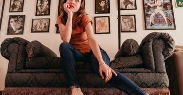 Mulher sentada no sofá olhando para o lado