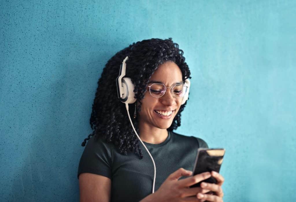 Mulher com fones do ouvindo, sorrindo, e digitando em um celular.