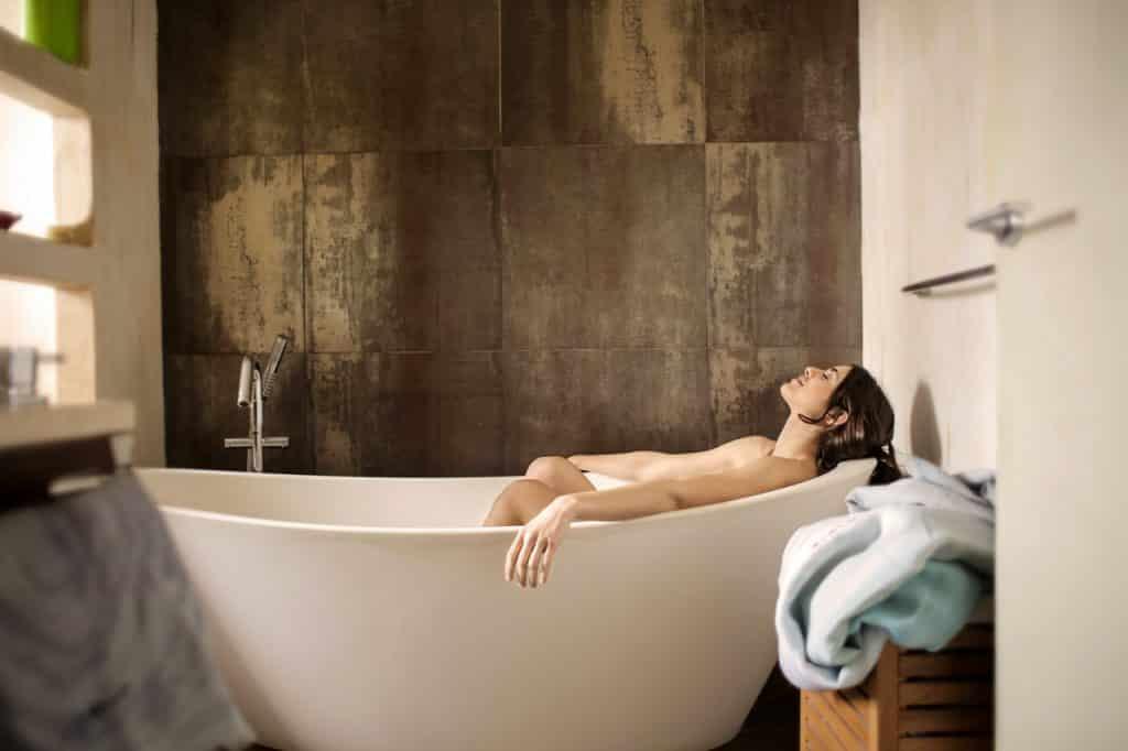 Mulher deitada dentro de banheira, com a cabeça inclinada para trás e os olhos fechados.