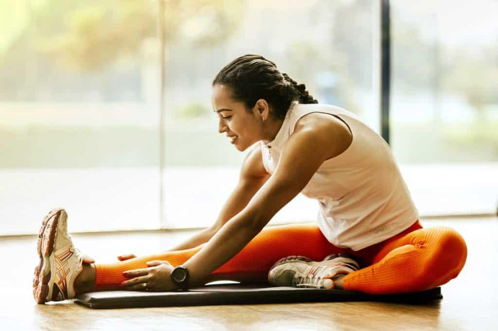 Mulher usando roupas de ginástica e sentada no chão estica uma perna para frente e seus braços até sua canela, em um alongamento.