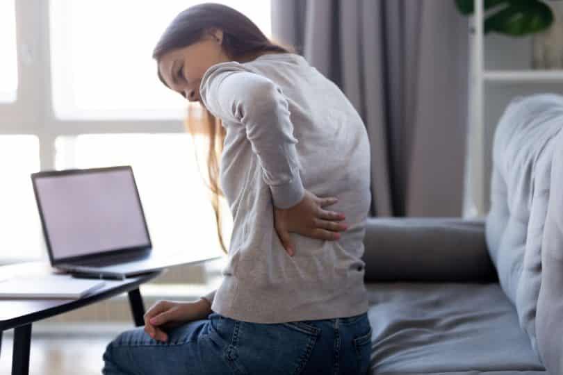Mulher branca com dor nas costas.