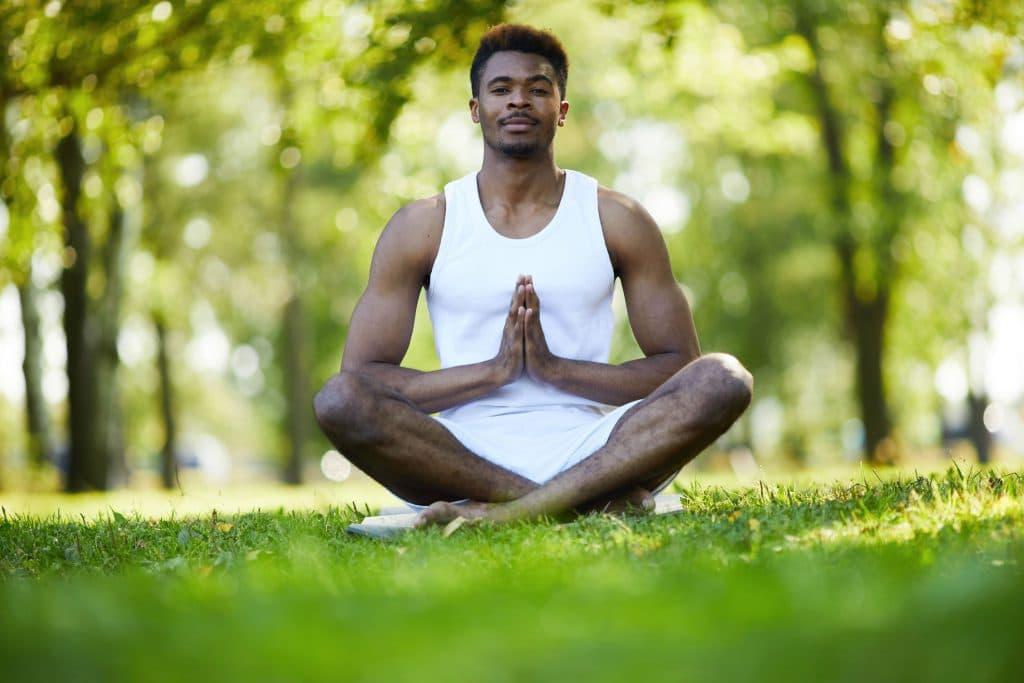 Homem sentado em pose de meditação em um parque.