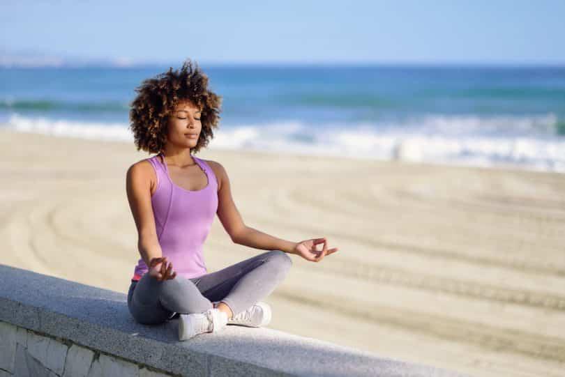 Mulher negra meditando com os olhos fechados na praia.