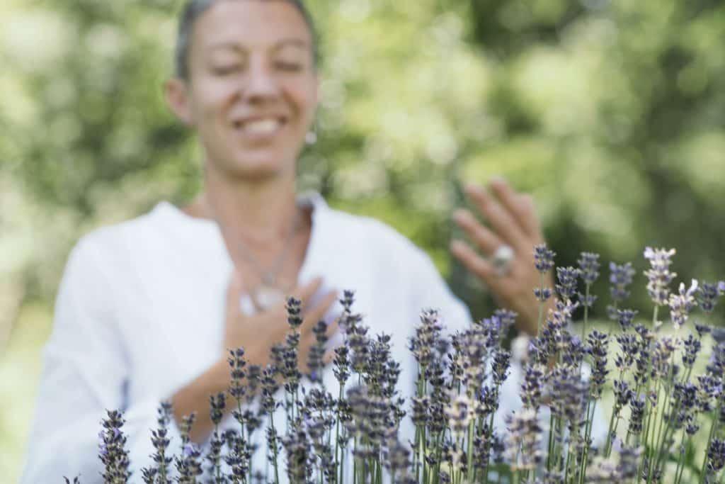 Mulher de olhos fechados sorrindo em frente a plantinhas