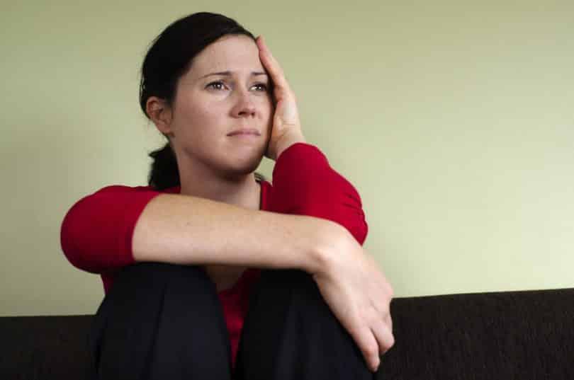 Mulher sentada com mão expressão preocupada e mão no rosto