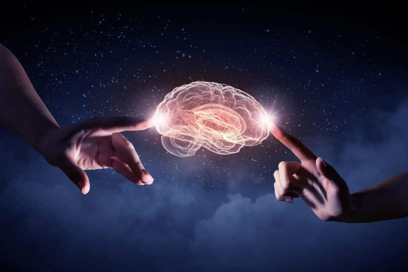 Ilustração de duas mãos tocando um cérebro brilhante em meio ao céu estrelado.