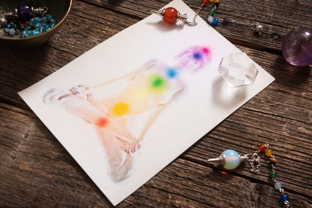 Desenho em papel branco de corpo humano esboçado em cinza, e os pontos coloridos representando os chacras no centro do corpo.