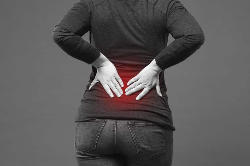 Recorte de uma pessoa de costas com as mãos no cóccix, pois está sentindo dores.