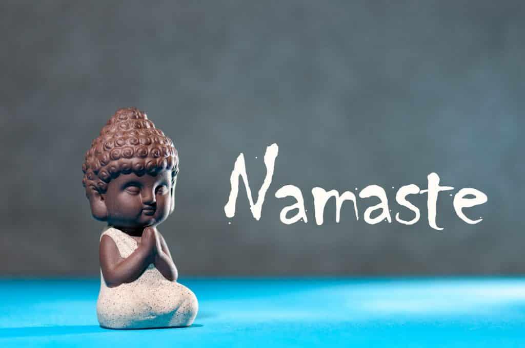 """Imagem de pequeno Buda em madeira, meditando, e a palavra """"namaste"""" escrito ao lado."""