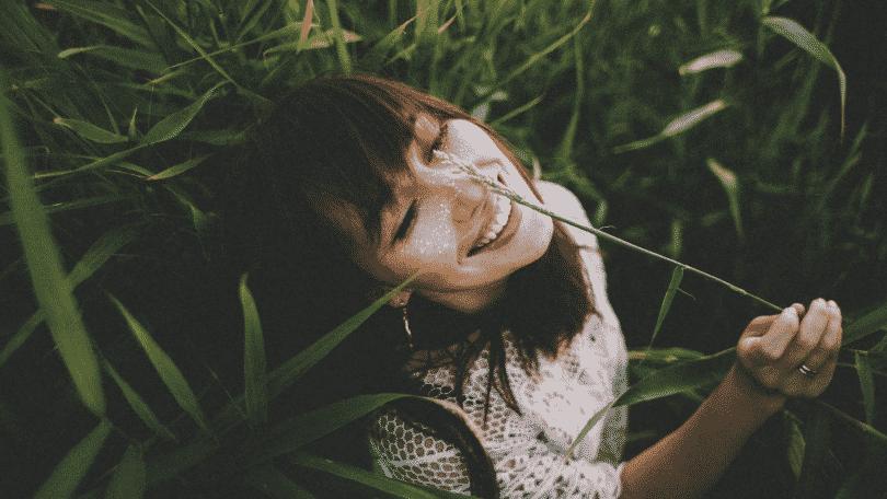 Menina sorrindo no meio de jardim