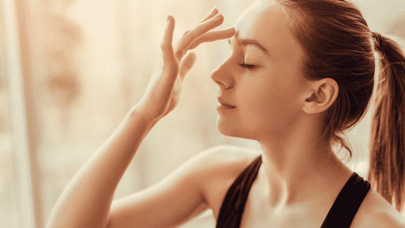Imagem de uma mulher com o dedo na testa, remetendo ao terceiro olho