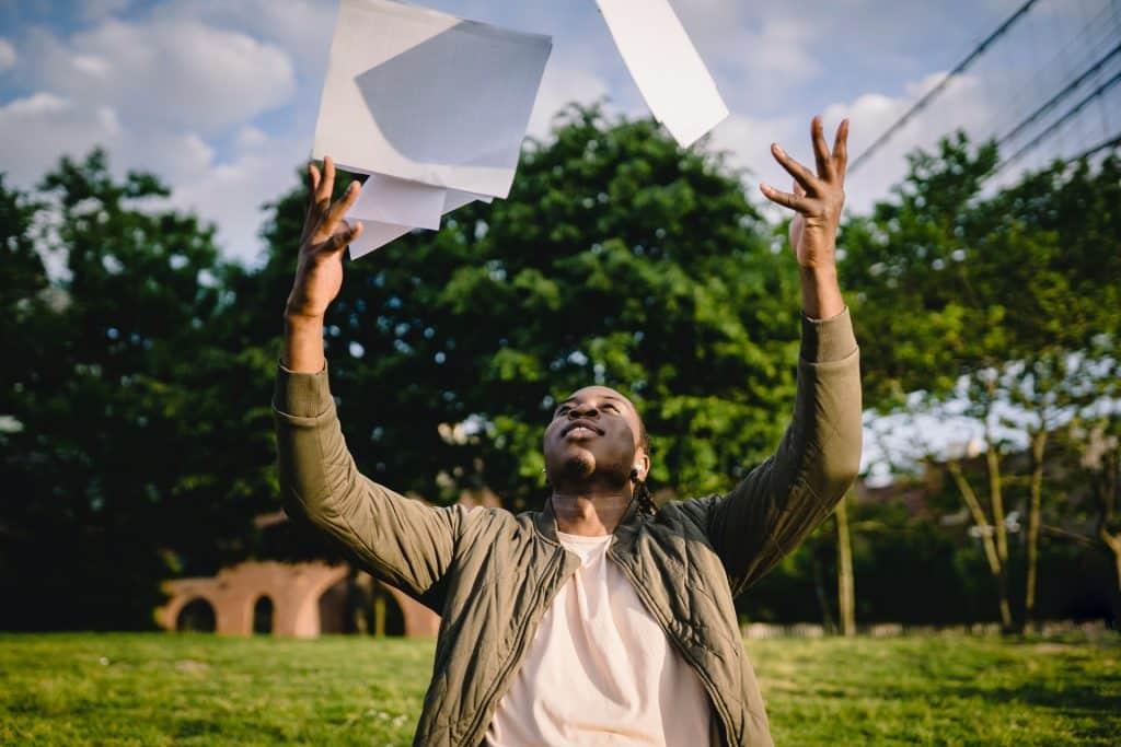 Homem em um parque durante o dia jogando papéis para cima enquanto sorri.