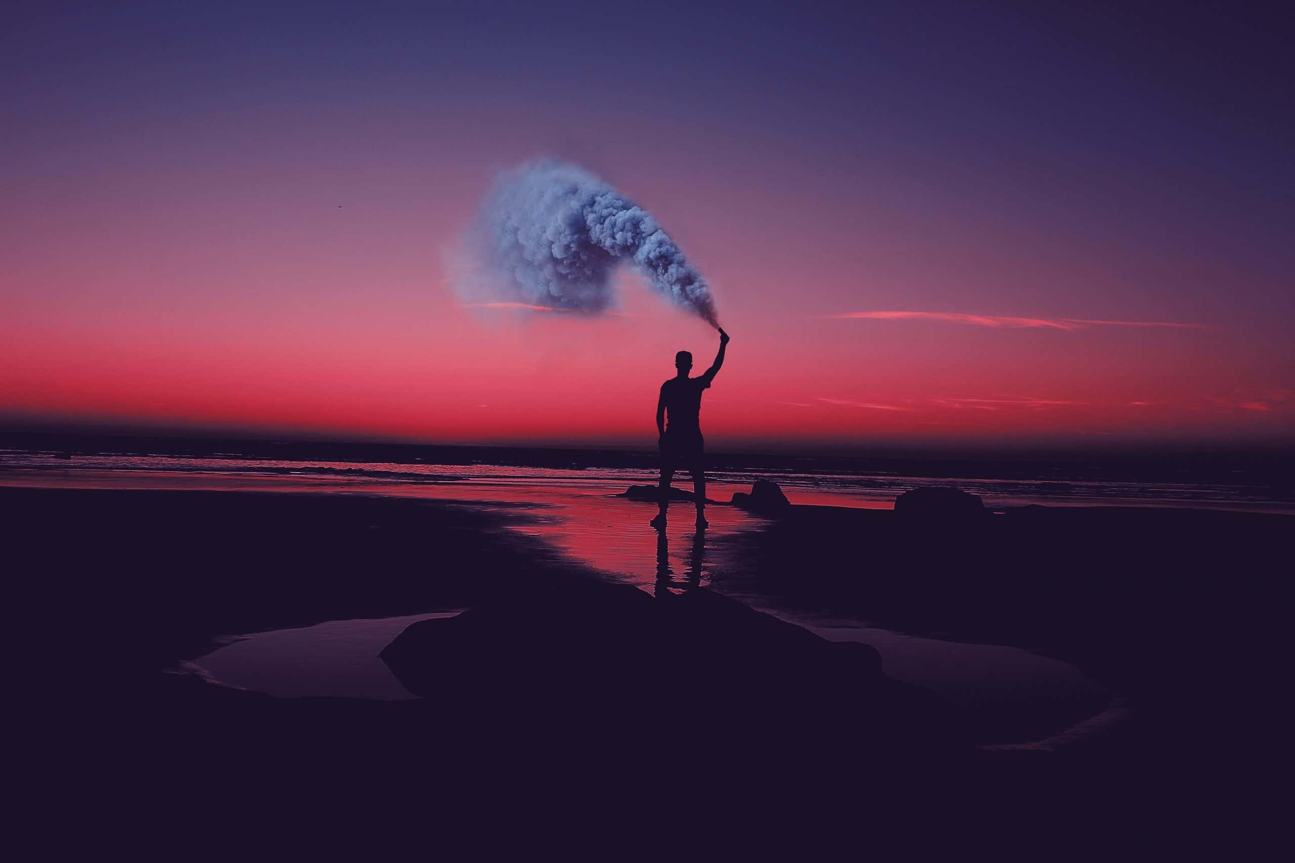 Homem em praia com céu avermelhado segurando tocha com fumaça