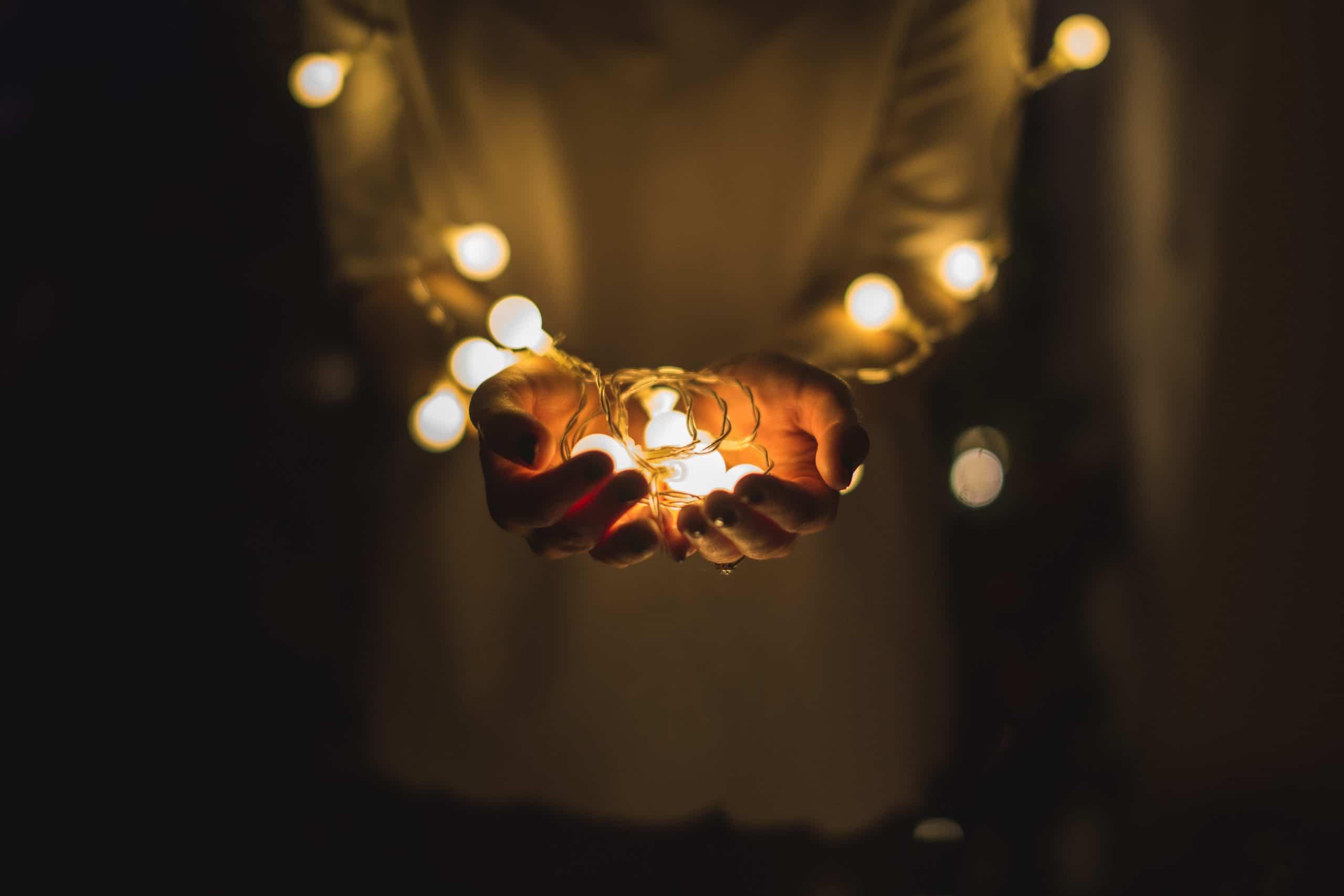Mãos segurando bolinhas de luzes em frente ao corpo