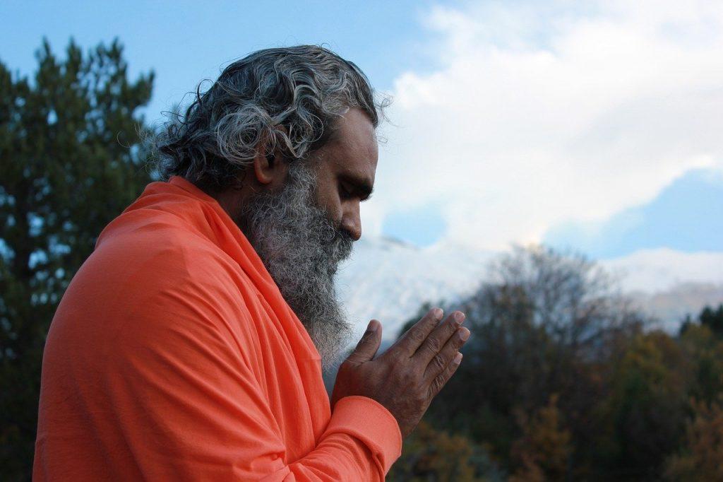 Homem indiano com cabelo e barba compridos e brancos, com os olhos fechados, meditando.