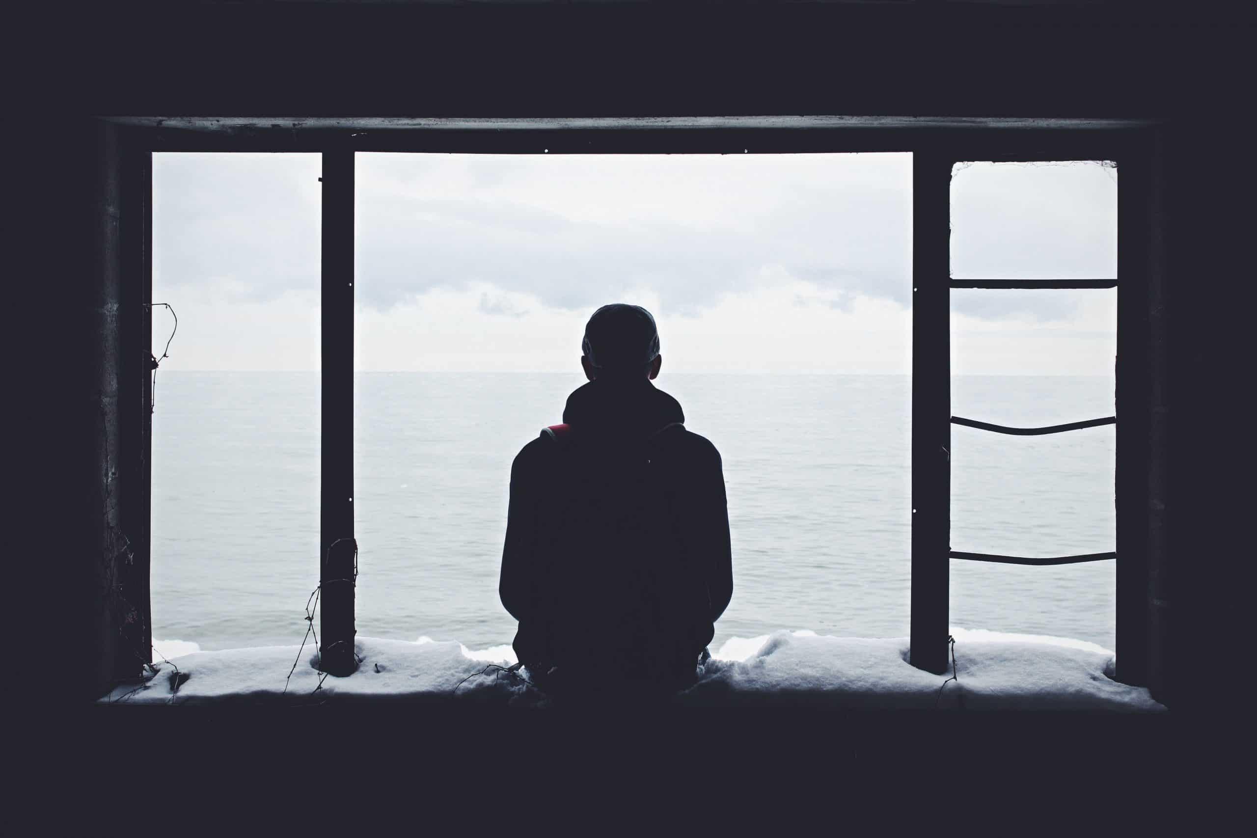 Homem de costas em janela de frente para o mar