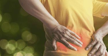 Mulher com a região do cóccix em vermelho com as mãos pressionadas no local