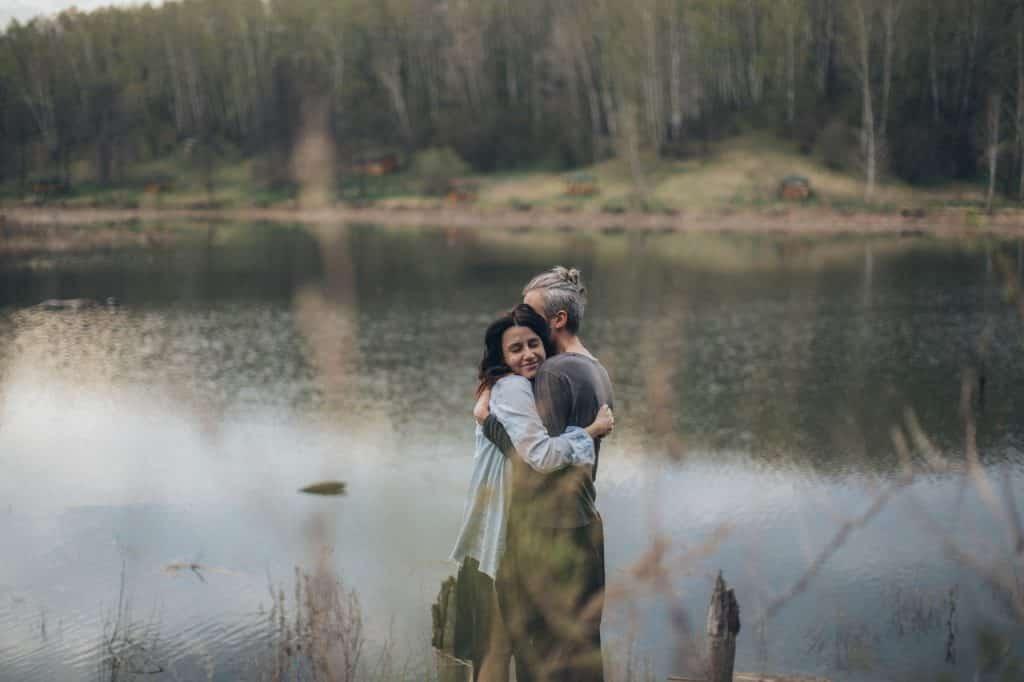 Duas pessoas se abraçando em frente a um lago, durante o dia