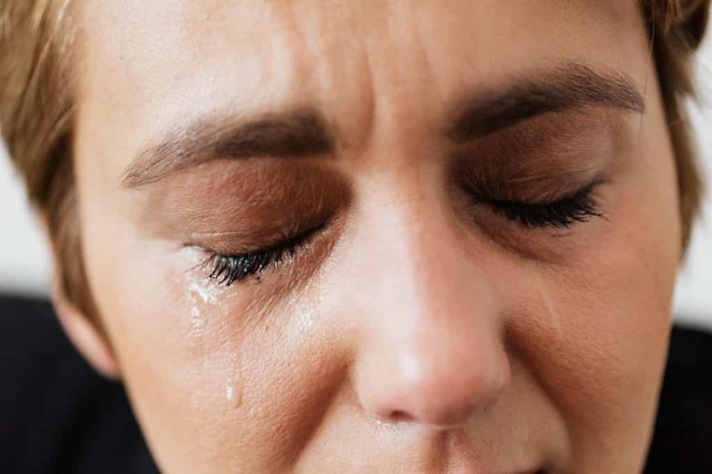 Imagem ampliada de uma mulher de olhos fechados enquanto lágrimas correm por seu rosto