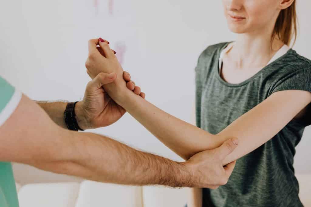 Mulher tendo seu braço examinado por um médico