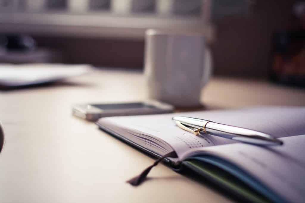 Mesa com caderno e caneta ao lado de uma xícara