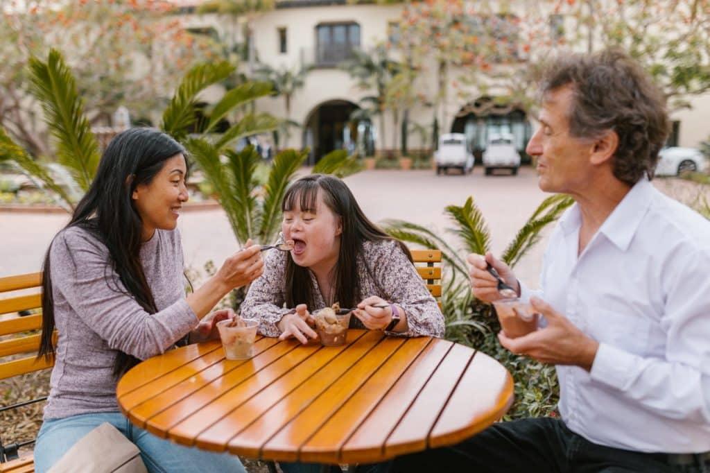 Menina autista sentada na mesa comendo com os pais.