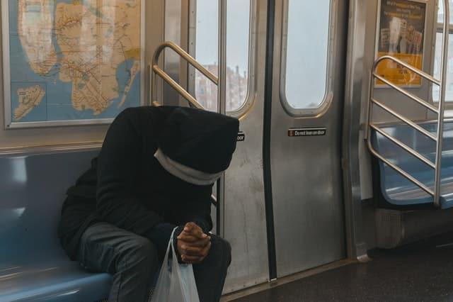 Homem sentado no metrô, com a cabeça baixa.