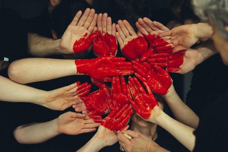 Mãos unidas formando coração com tinta vermelha