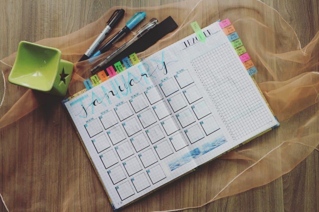 Imagem de um calendário do mês de Janeiro feito à mão em um caderno, ao lado de canetas coloridas.