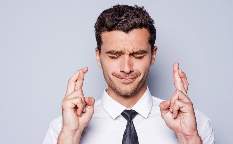 Homem usando camisa e gravata com dedos cruzados e olhos fechados