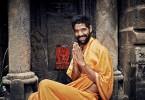 Homem indiano com trajes típicos, sorrindo e fazendo a añjalimudra.