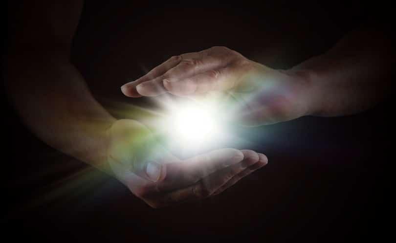 Duas mãos envolvendo uma luz
