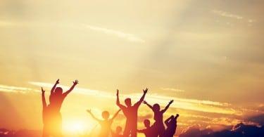Pessoas com braços para o alto e pôr-do-sol ao fundo