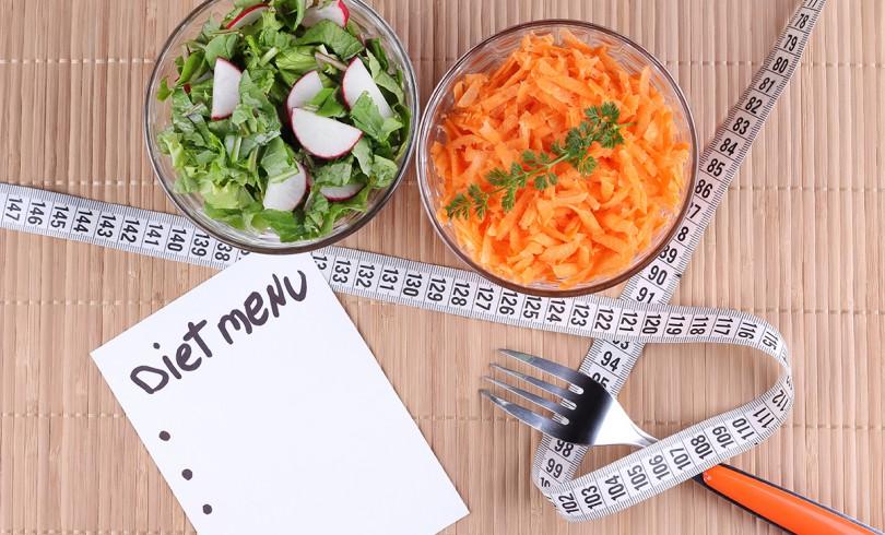 Pratos de saladas vistas de cima com garfo, fita métrica e lista de menu