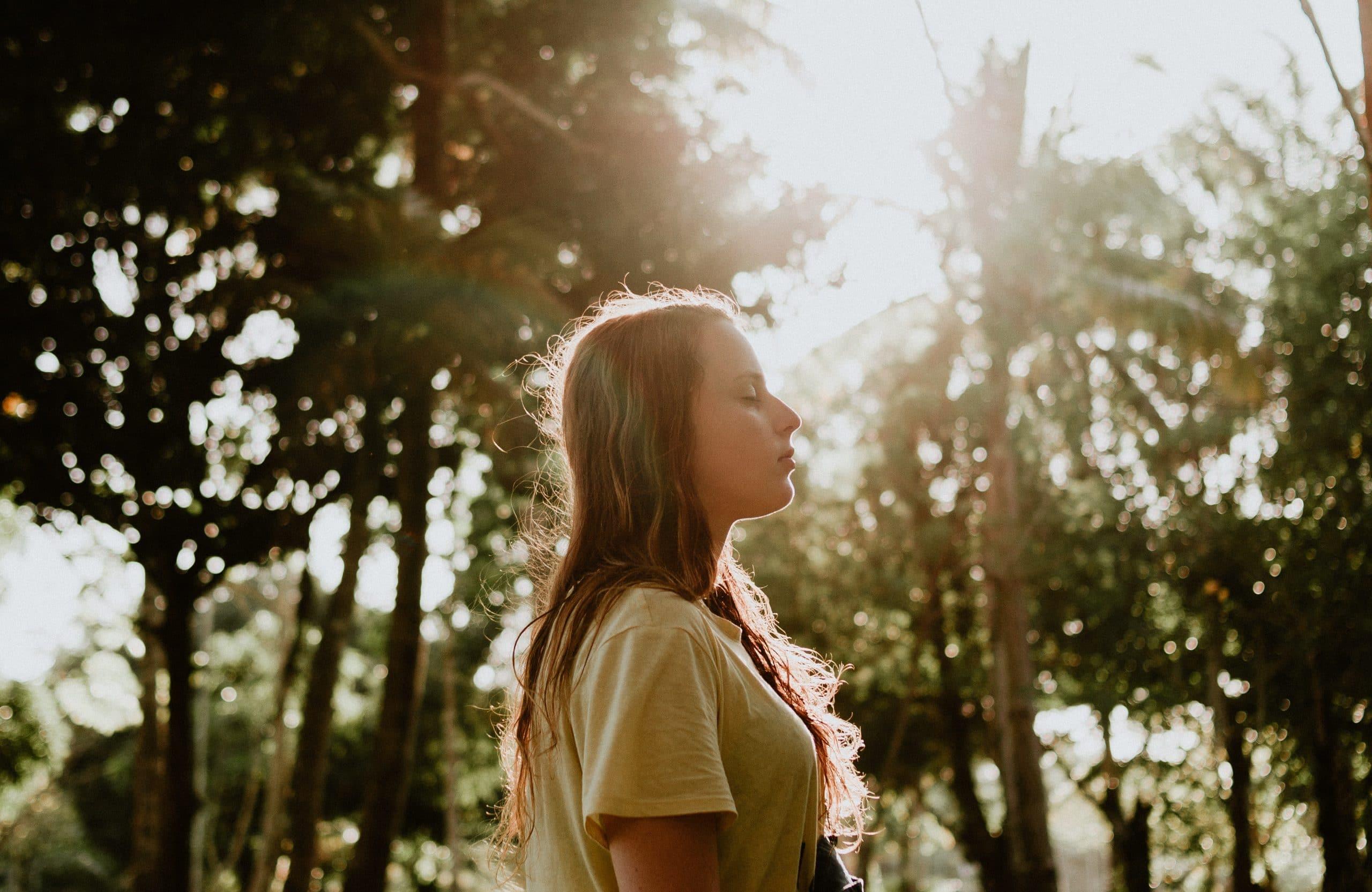 Mulher de olhos fechados com árvores e sol refletindo ao fundo