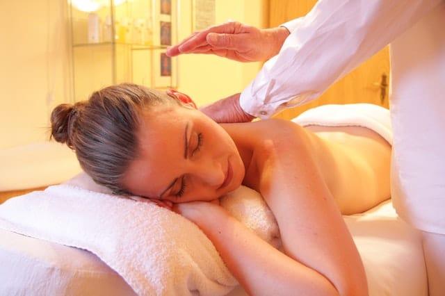 Mulher deitada recebendo massagem nas costas