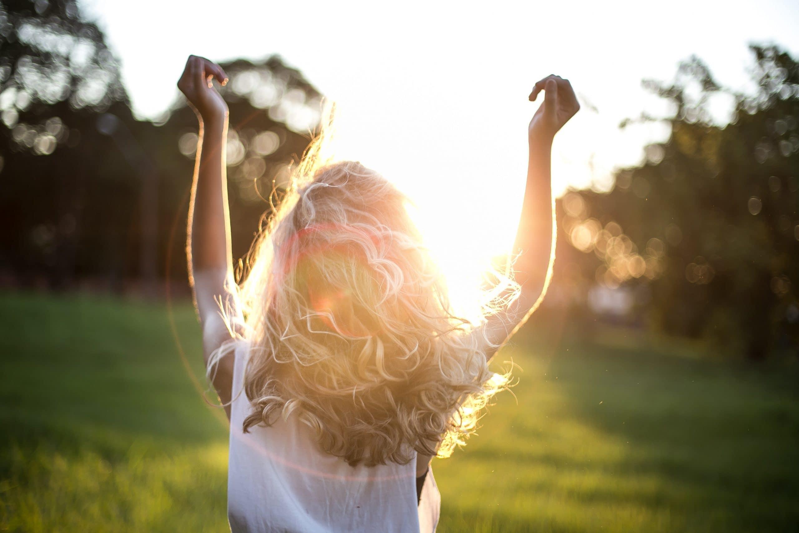 Mulher de costas com as mãos para cima com sol refletindo