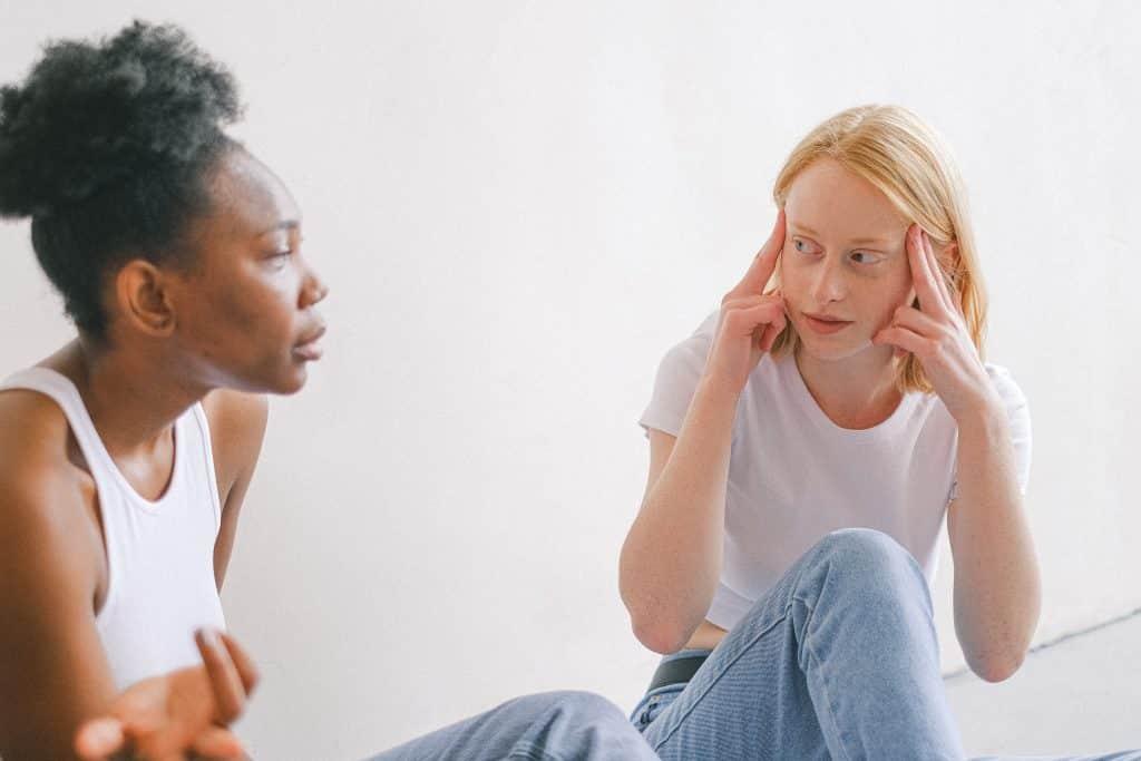 Duas mulheres sentadas conversando enquanto uma coloca os dedos sobre os lados de sua cabeça.