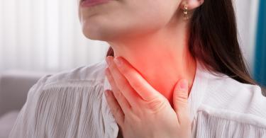 Mulher sofrendo de dor de garganta