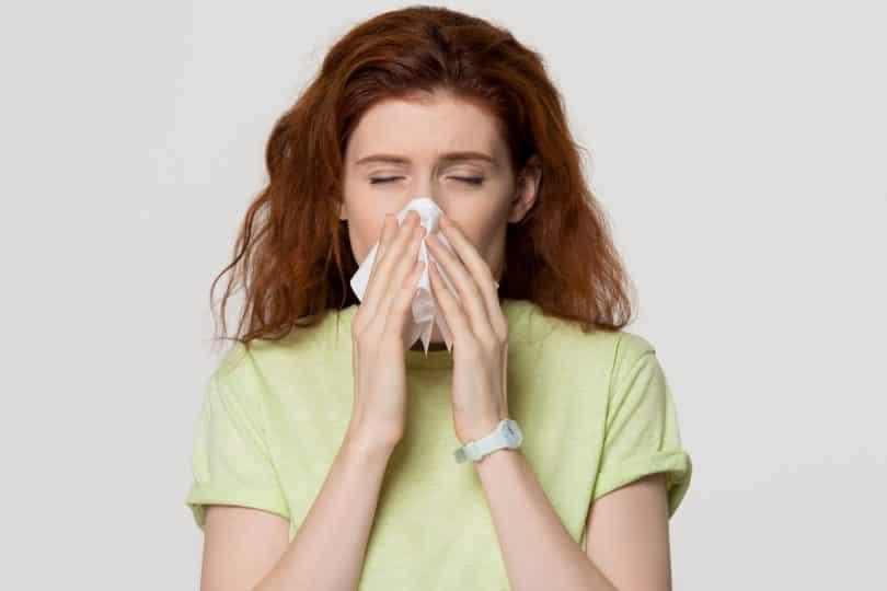 Mulher ruiva doente assoando o nariz.
