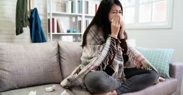 Mulher asiática sentada num sofá, envolta de manta xadrez, enquanto assoa o nariz.