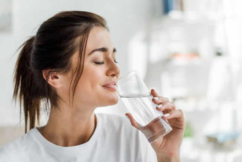 Mulher de olhos fechados bebe água.