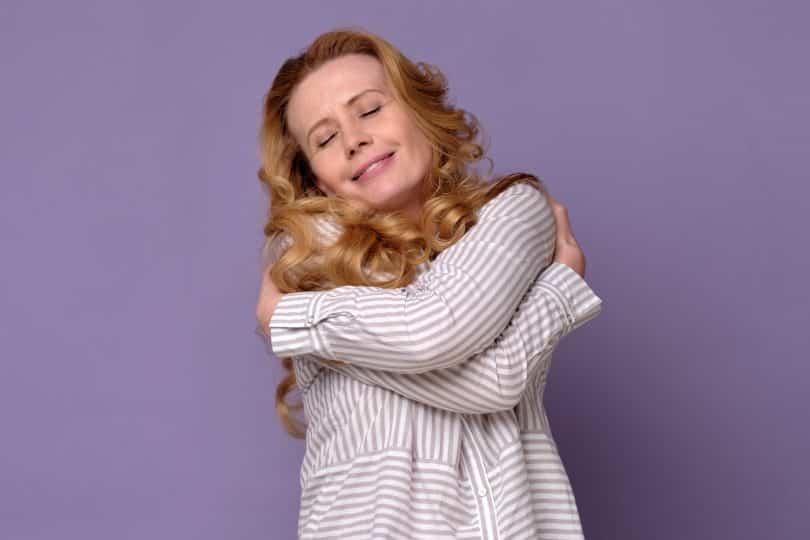 Mulher abraça a si mesma e sorri. Ela está em um cenário roxo.