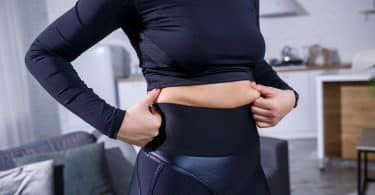Mulher branca segurando sua barriga.