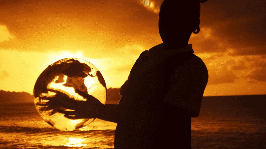 Silhueta de pessoa segurando um globo de plástico sob o por do sol
