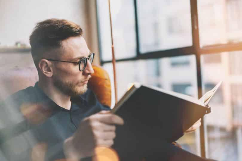 Homem branco lendo livro.