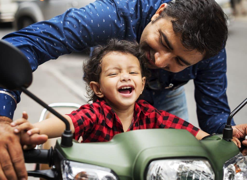 Criança hindu brincando com o pai.