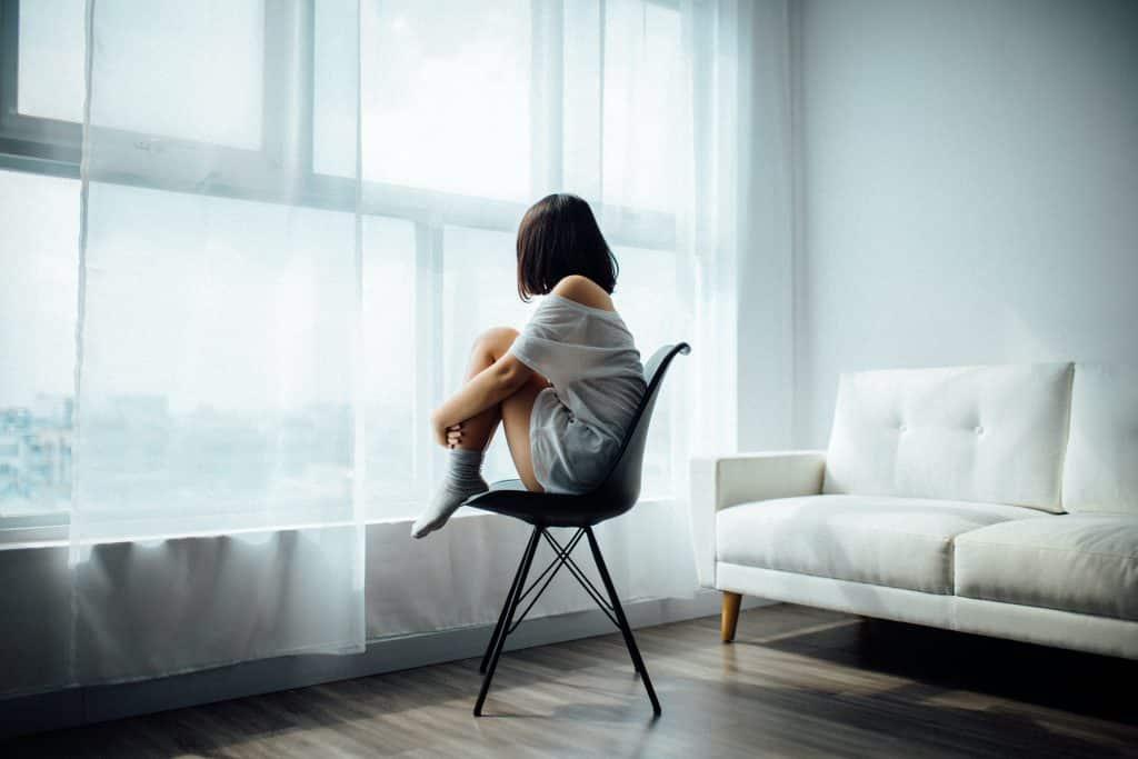 Mulher sentada em uma cadeira de frente para sua janela com cortinas