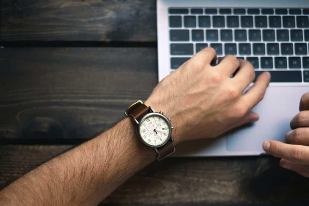 Homem olhando para seu relógio de pulso