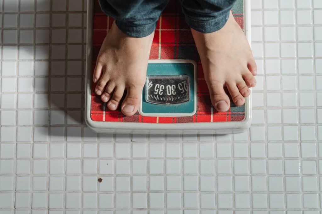 Pés de uma pessoa que usa calças jeans sobre uma balança.